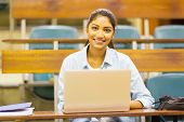pretty female indian college student using a laptop in lecture room