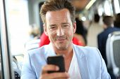 Mature man in tramway using smartphone