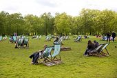LONDON, UK - MAY 14, 2014  - Brits chilling up in Green park near the Buckingham palace
