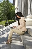 businesswoman with laptop at staircase