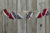 Country plaid Christmas hearts hanging on clothesline by rustic wooden background