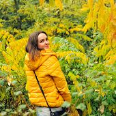 Young cute woman in yellow hoody walking in autumn forest.
