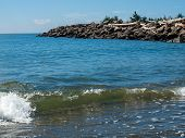Gentle Beach Waves With A Rock Jetty