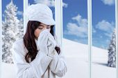 pic of sneezing  - Pretty girl wearing jacket and using a tissue for sneezing at home in winter day - JPG