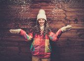 Smiling woman in ski jacket and white hat standing against wooden house wall under snow