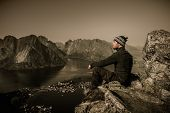 Man hiker looking at Reine village panorama, Norway