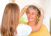 stock photo of geriatric  - Caregiver put the hat on the happy elderly womans head - JPG