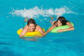 Cheerful young couple in inflatable rings at swimming pool
