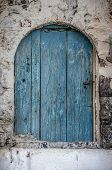 Old blue timber door in the scuffed wall