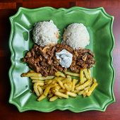 Beef Stroganov/Beef Stroganoff with fries, rice and mushrooms on the green plate