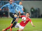 KLAGENFURT, AUSTRIA - MARCH 05, 2014: Diego Godin (#3 Uruguay) and Zlatko Junuzovic (#10 Austria) fight for the ball in a friendly soccer game between Austria and Uruguay.