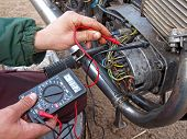 stock photo of dynamo  - Checking the motorcycle engine generator with multimeter - JPG