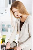 Young woman cooking soup in the kitchen