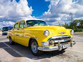 HAVANA,CUBA - OCTOBER 31,2014 : Colorful yellow vintage car with a blue sky and puffy clouds