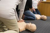 stock photo of cpr  - A group of adult education students practitcing CPR chest compressioon on a dummy.