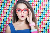 Attractive surprised young woman wearing glasses on spotted background, beauty and fashion concept