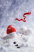 Melting snowman with red knitted scarf blowing in the wind