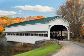 stock photo of covered bridge  - The historic Westport Covered Bridge crosses Sand Creek in rural Decatur County Indiana backed by colorful autumn foliage - JPG
