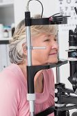 image of slit  - Beautiful senior patient looking into slit lamp at clinic - JPG