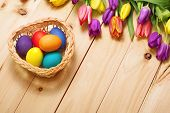 stock photo of gift basket  - Spring Flowers bunch and easter eggs at wood floor texture - JPG