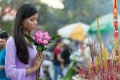 stock photo of buddhist  - Peace and beauty in prayer as a young Vietnamese woman makes an offering of pretty fresh pink flowers at a Buddhist shrine with burning incense - JPG