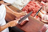 pic of slaughterhouse  - High angle portrait of smiling butcher cutting meat at counter in butchery - JPG