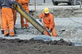 image of concrete pouring  - Worker leveling concrete poured from mixer on construction site - JPG