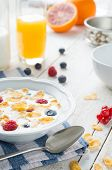 picture of fruit bowl  - A glass of orange juice and a bowl of milk with cornflaks and fruit on a rusti table - JPG