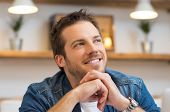 foto of thinking  - Closeup of smiling young businessman thinking in office  - JPG