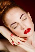 image of freckle face  - Beautiful young model with red lips and red nail polish on a black background - JPG