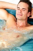 picture of hot-tub  - Young man relaxing in hot tub - JPG