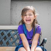 image of sitting a bench  - Little girl sits laughing on outside bench - JPG