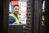 foto of forklift driver  - Smiling driver operating forklift machine in warehouse - JPG