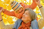 stock photo of grandmother  - Grandmother with her granddaughter for a walk during the fall of the leaves in the park - JPG