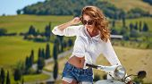 foto of scooter  - Young beautiful italian woman sitting on a italian scooter in tuscany outdoor  - JPG