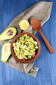 picture of avocado  - Salad with apple and avocado in bowl with napkin on wooden background - JPG