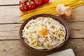 stock photo of carbonara  - pasta carbonara on a plate with egg yolk and parmesan cheese