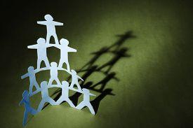 stock photo of human pyramid  - Human team pyramid on green background - JPG