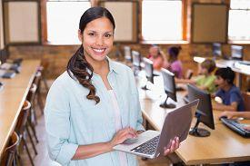 stock photo of teachers  - Pretty teacher using laptop in computer class at the elementary school - JPG