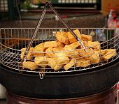 image of stinky  - An outdoor vendor offers deep fried chunks of stinky fermented tofu a popular Chinese snack - JPG