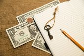 image of memento  - Opened notebook with a blank sheet pencil key and money on the old tissue - JPG