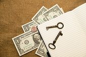 stock photo of memento  - Opened notebook with a blank sheet keys and money on the old tissue - JPG