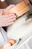 pic of flour sifter  - Flour sifting through a sieve for a baking - JPG