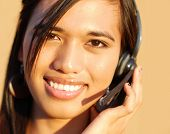 Young attractive friendly customer service answering customer questions on the telephone