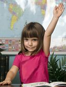 Cute little girl with arm raised in class to answer a question