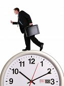 stock photo of hustle  - A handsome business man running on a large clock - JPG