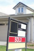 House sold sign on sign board outside home