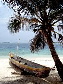 tropical white sand beach with a canoe