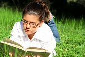 Teenager laying on grass reading a book