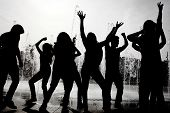 silhouette of young people dancing at a party near a water fountain
